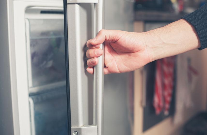 Mão em close abrindo um freezer de inox.