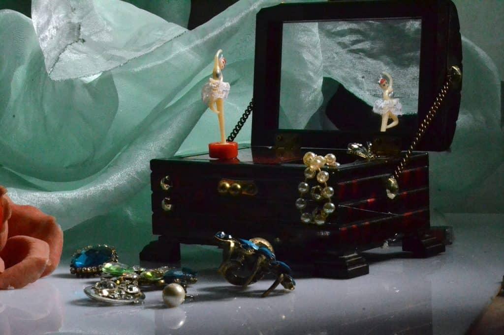Imagem de caixinha de música com boneca e joias em volta.