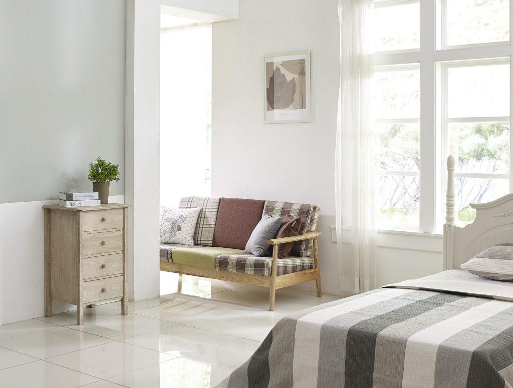 Imagem de cama de solteiro coberta com lençol listrado em tons de cinza, em quarto com sofá e cômoda.