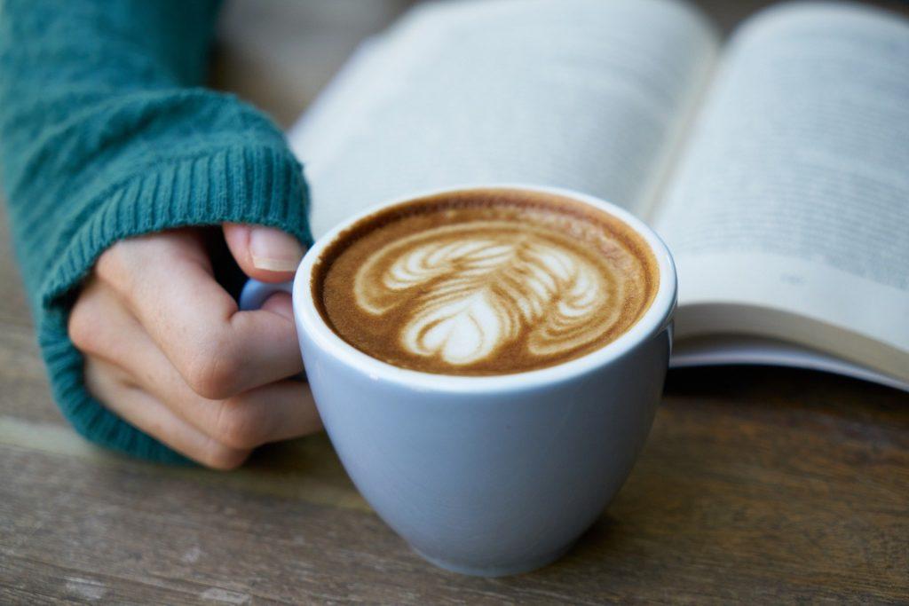 Imagem de pessoa lendo um livro enquanto segura uma caneca com café