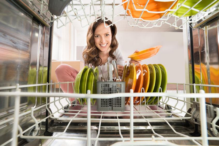 Imagem de dentro de uma lava louças para fora com mulher sorrindo em frente.