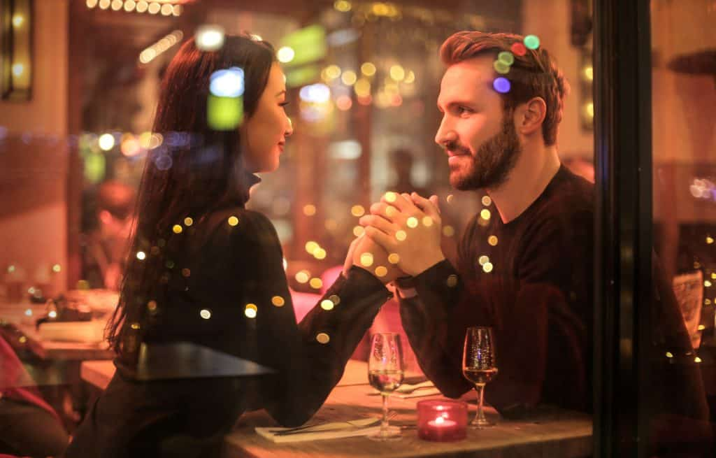 Na foto um casal sentado em uma mesa de restaurante se olhando.