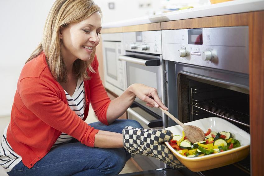 Mulher agachada em frente a um forno de embutir mexendo os vegetais em uma travessa.