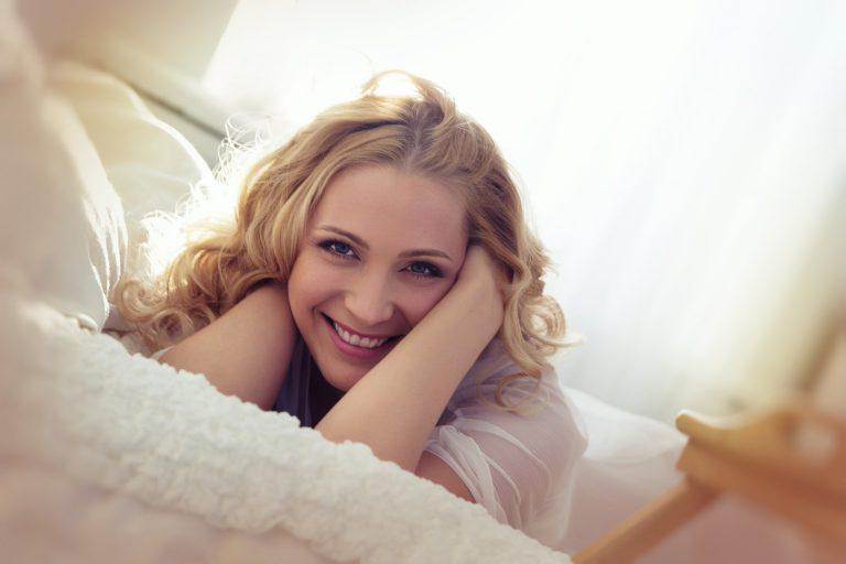 mulher deitada na cama de bruços olhando para a câmera e sorrindo