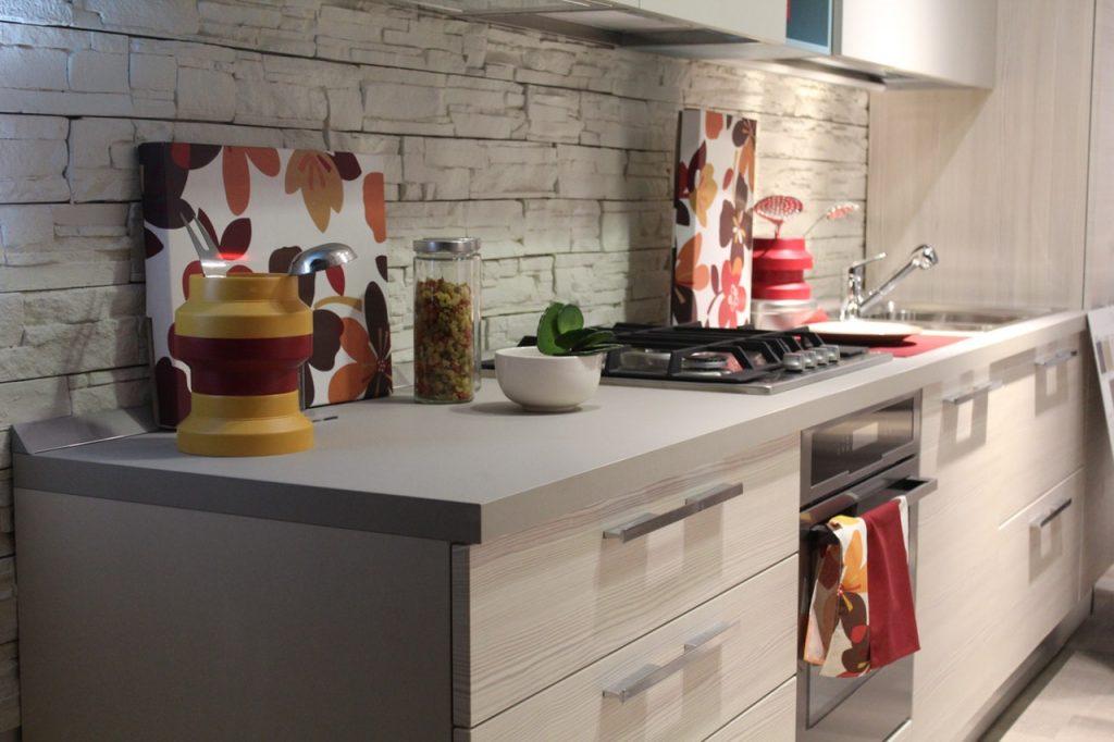 Na foto a bancada de uma cozinha com quadros floridos, armário, um cooktop e um fogão.