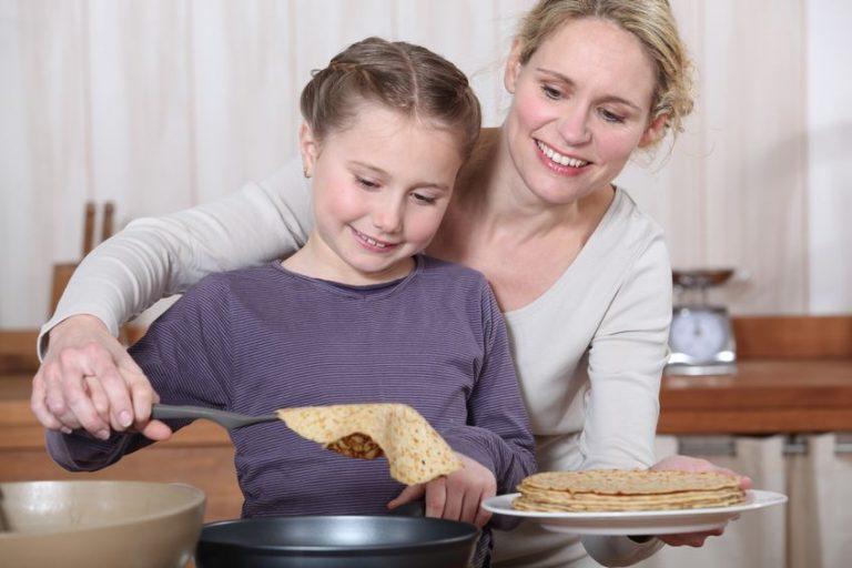 Mãe e filha preparam panquecas usando panquequeira