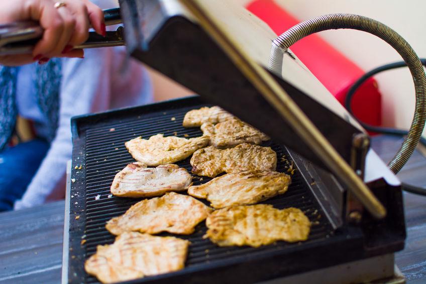 Mãos manejam filés de frango sendo grelhados em grill elétrico