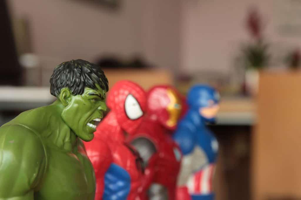 Na foto quatro bonecos de super-herói com uma mesa ao fundo.