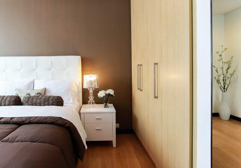 Cama Box e criado mudo, com parede marrom ao fundo e armário de madeira ao lado