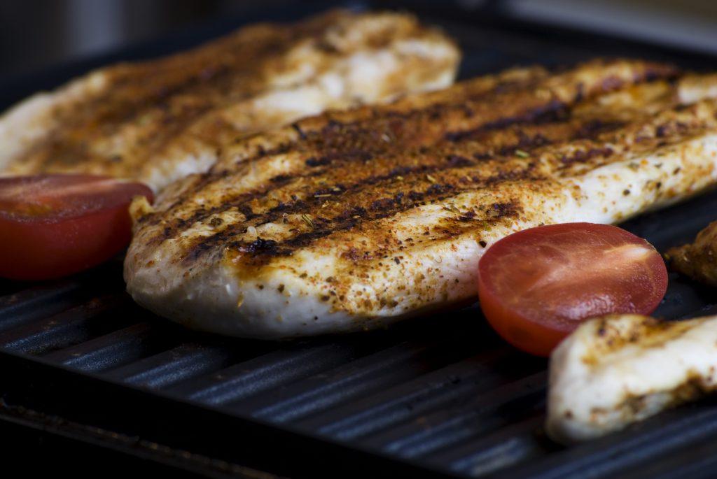 Imagem aproximada de grill com filé de frango e tomates