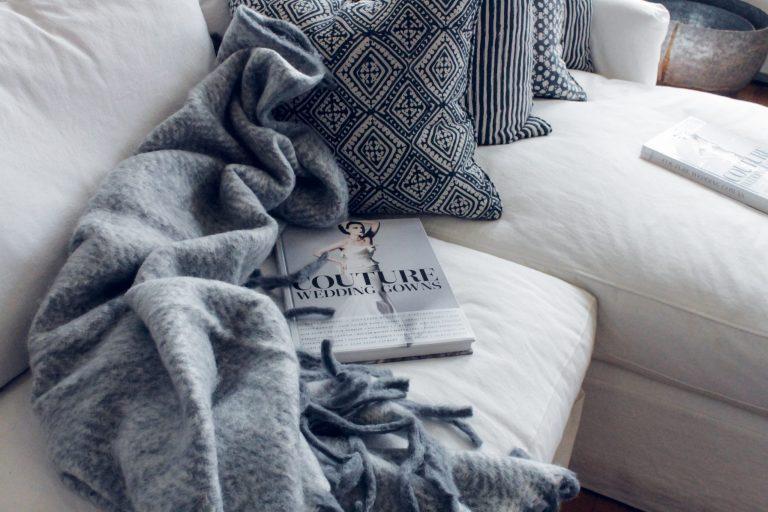 Na foto um sofá com uma manta e algumas almofadas cinzas.