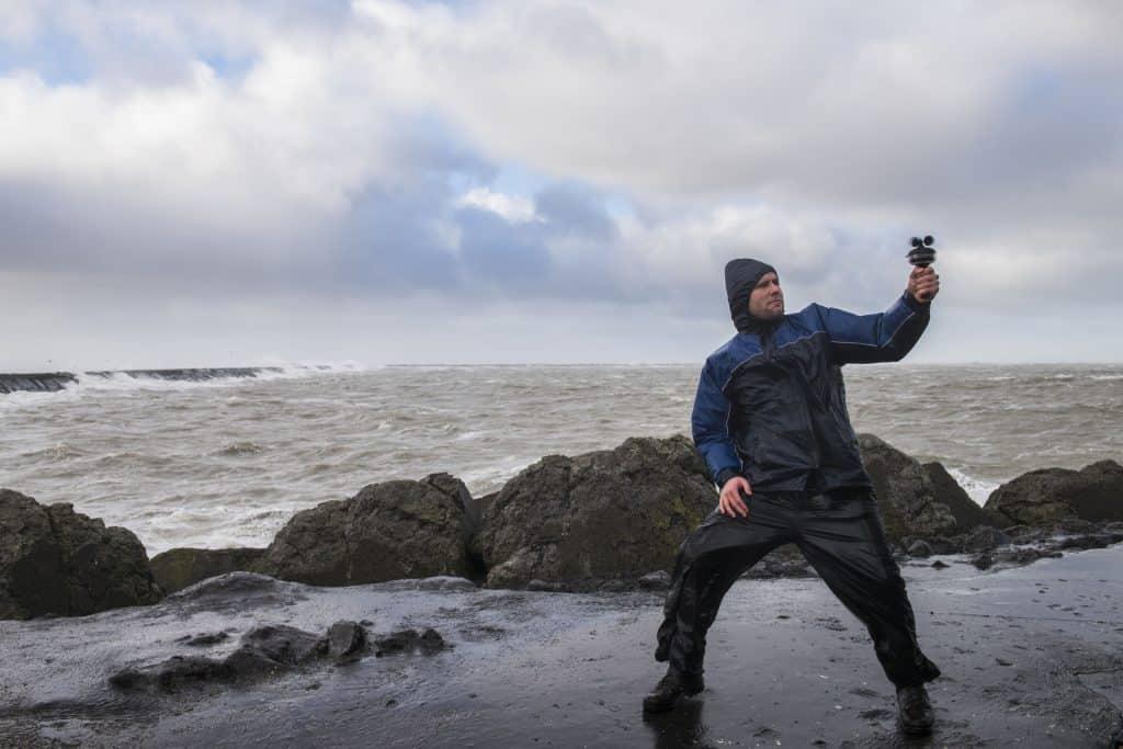 Um homem usando um anemômetro para medir o vento em uma praia com areia molhada.