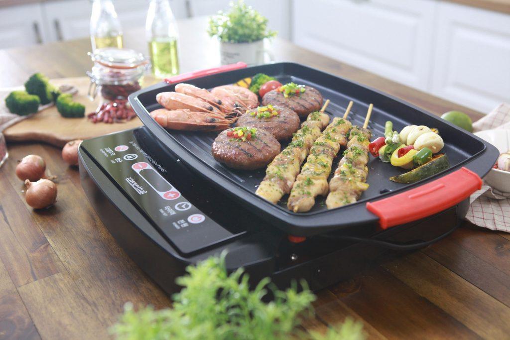 Camarões, carne, frango e vegetais sendo preparados ao mesmo tempo em grill elétrico