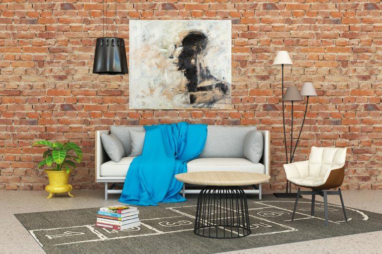 Na foto uma sala de estar com parede de tijolo, um sofá, uma poltrona abajures e quadro na parede.