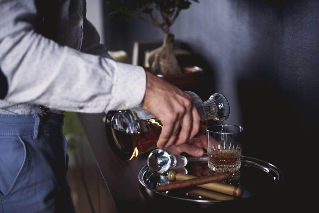 Rapaz serve whisky em copo sobre bandeja direto de licoreira.