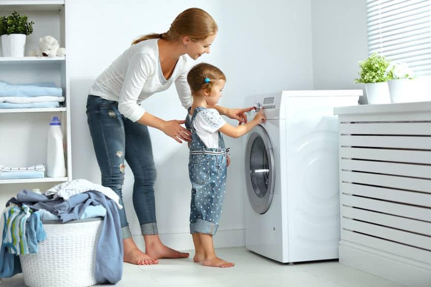 Na foto uma mulher e uma criança em frente a uma máquina de lavar.