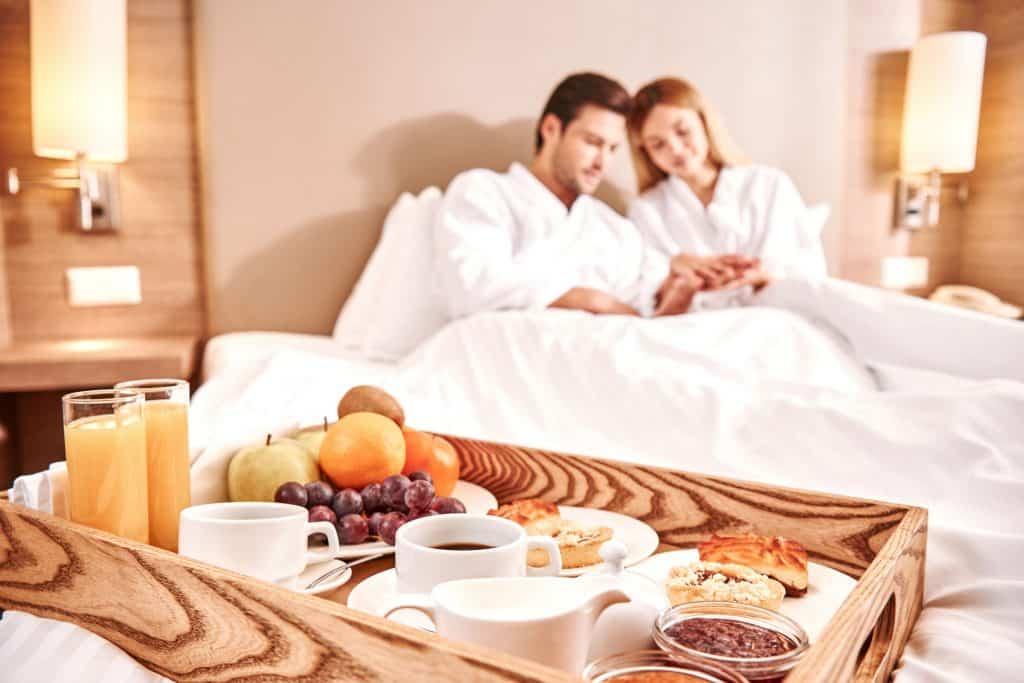 Bandeja de café da manhã na cama com casal recostado ao fundo.