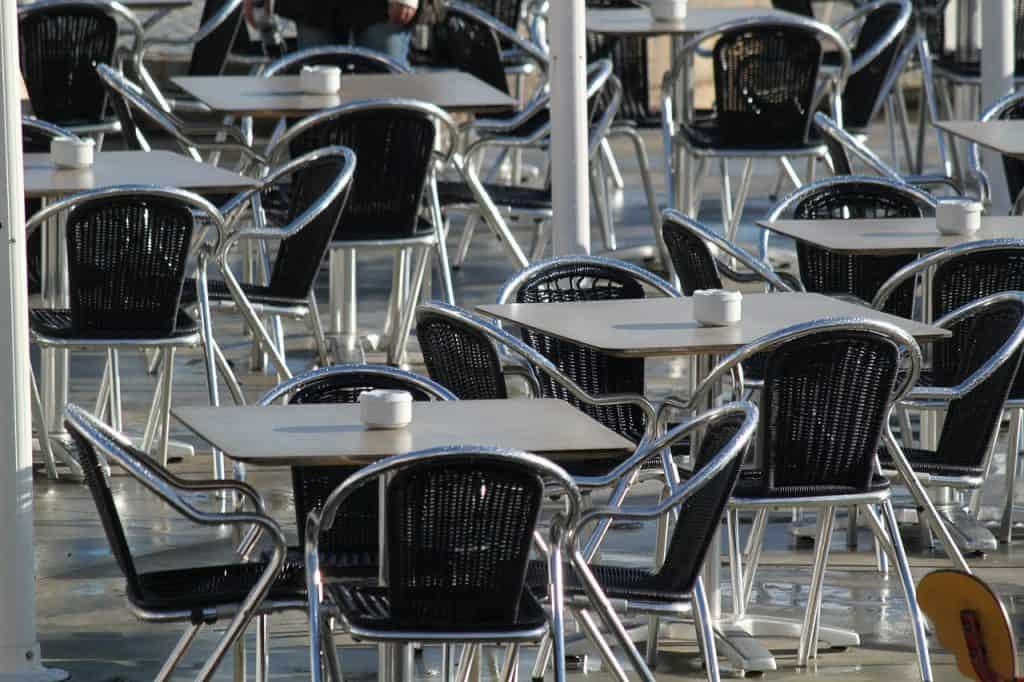 Diversas mesas e cadeiras de metal. Em cada uma das mesas há um cinzeiro branco.