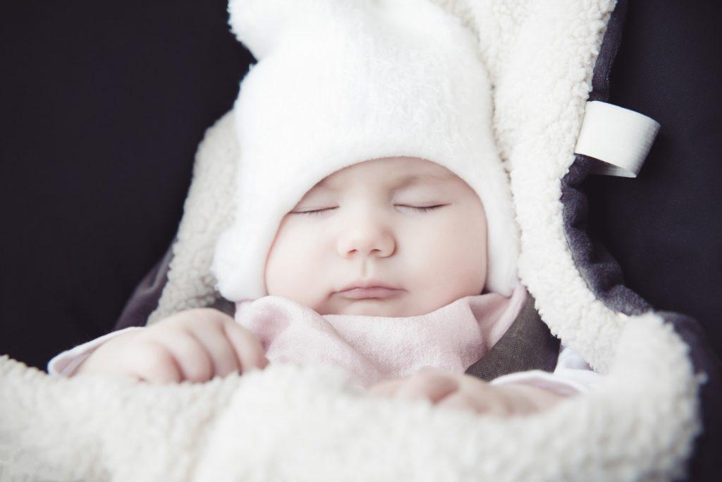 Imagem de bebê envolta em manta térmica branca e cinza