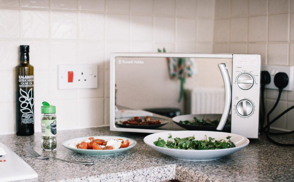 Micro-ondas sobre bancada de cozinha com alimentos ao lado aguardando para serem aquecidos