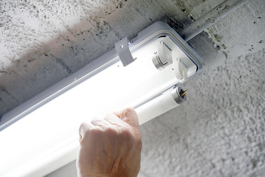 Imagem de pessoa realizando a instalação de uma lâmpada tubular