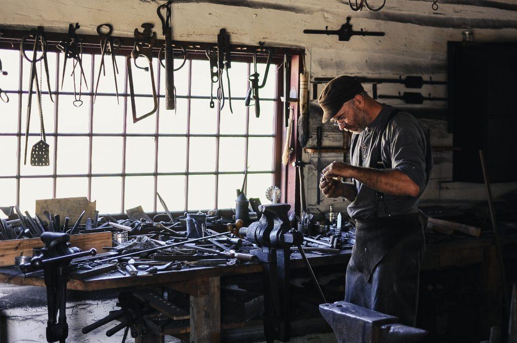 Imagem mostra um homem em uma oficina com diversas ferramentas.