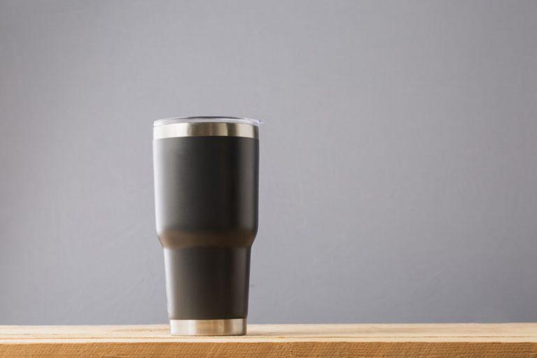 Na foto um copo térmico em cima de uma superfície de madeira.