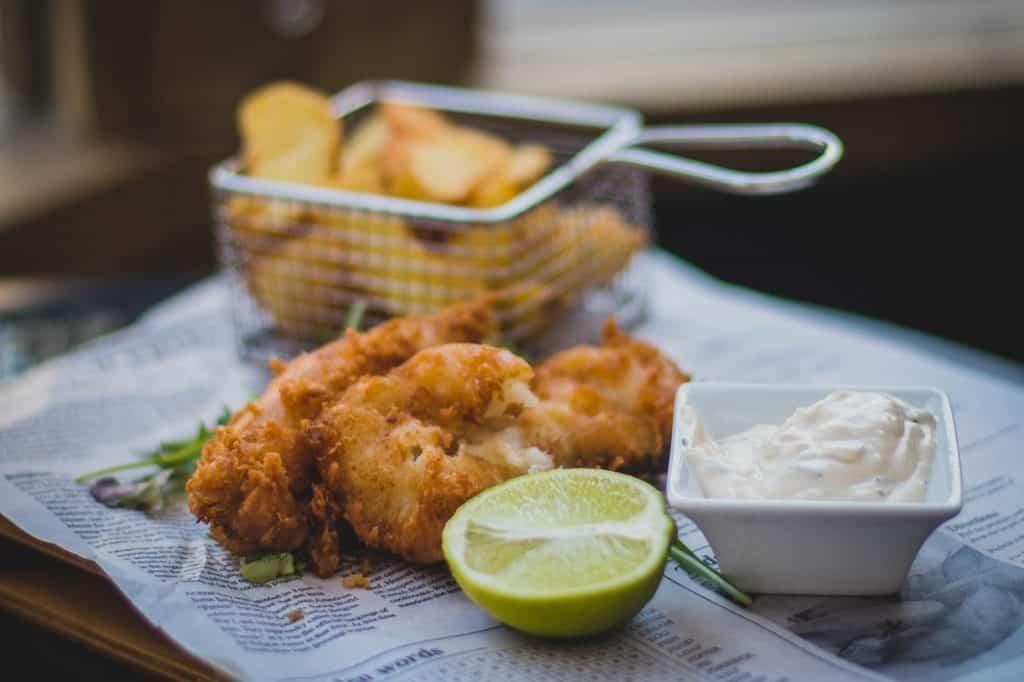 Imagem de peixe frito com limão, molho e uma escumadeira em formato de balde com batatas fritas.