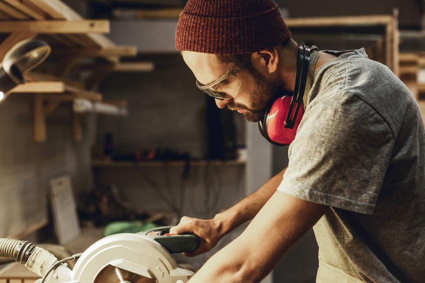 Imagem mostra um homem usando uma serra circular de bancada.