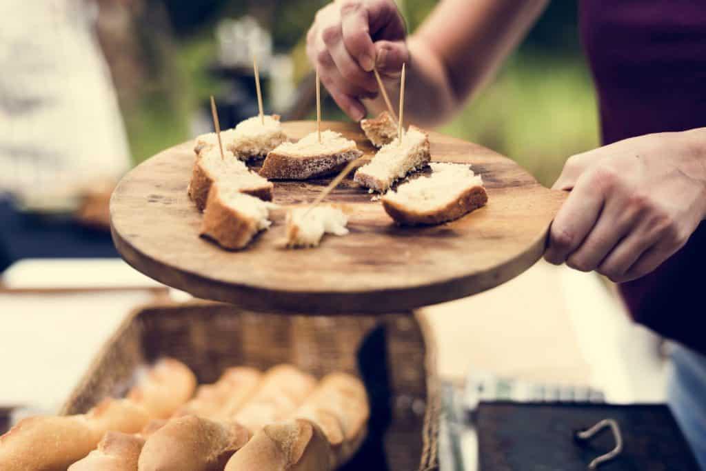 Homem masculina segurando uma tábua com pedaços de pão espetado no palito.