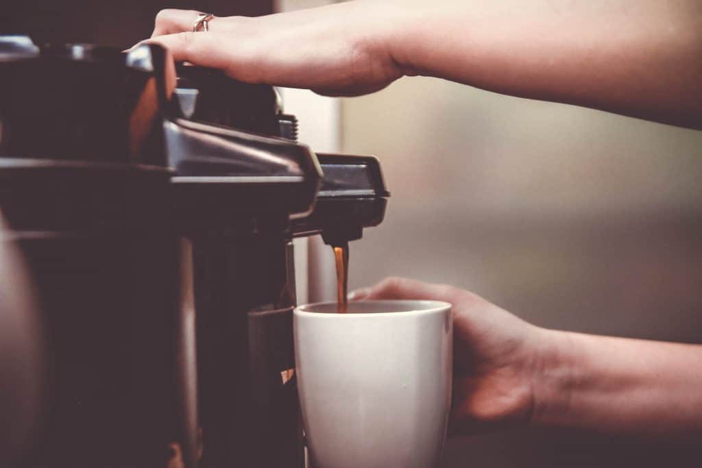 Uma pessoa está segurando uma caneca branca enquanto simultaneamente manuseia uma cafeteira que despeja o café para dentro do objeto.