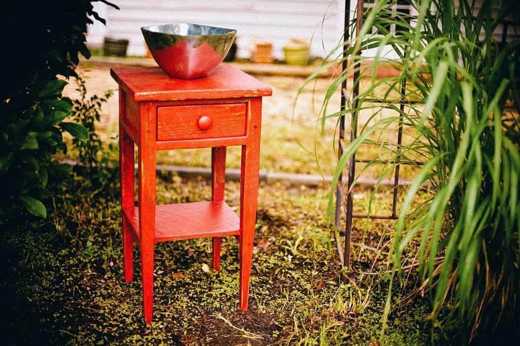 Mesa de canto vermelha, com uma gaveta e uma tigela em cima. Ela está no que parece um jardim.