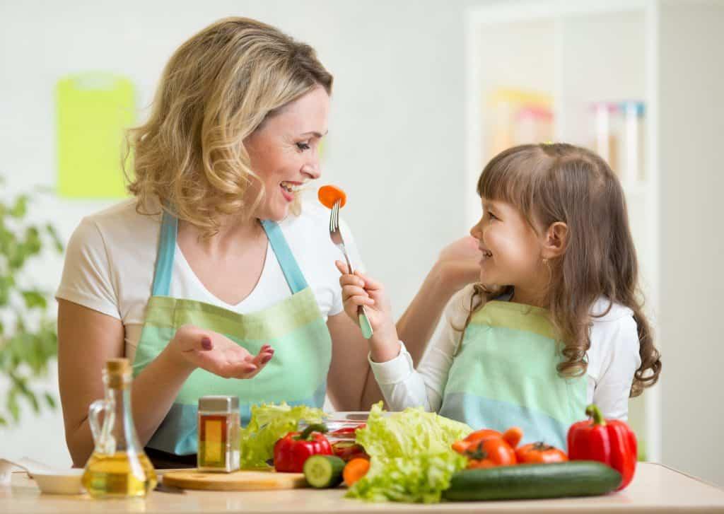 Na foto uma mulher com uma criança com legumes em uma mesa e um galheteiro sobre ela.