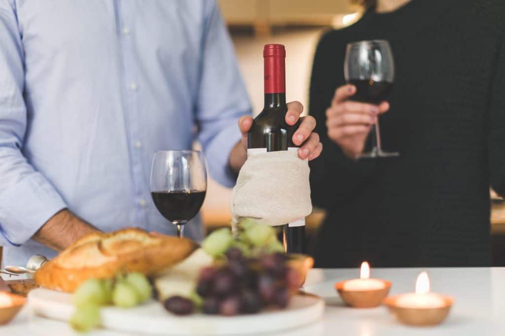 Na foto duas pessoas segurando taças de vinho com uma garrafa e uma mesa na frente.