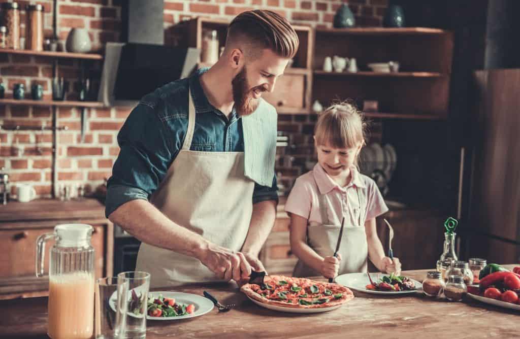 Homem corta pizza com cortador circular enquanto é observado por garotinha sorridente com talheres em punho.