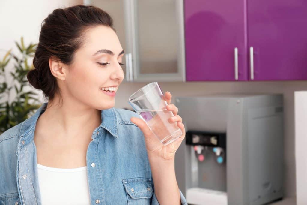 Mulher bebendo água, com cozinha e purificador de água ao fundo.