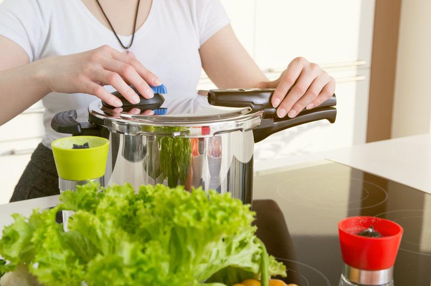 Na foto uma mulher fechando uma panela de pressão.