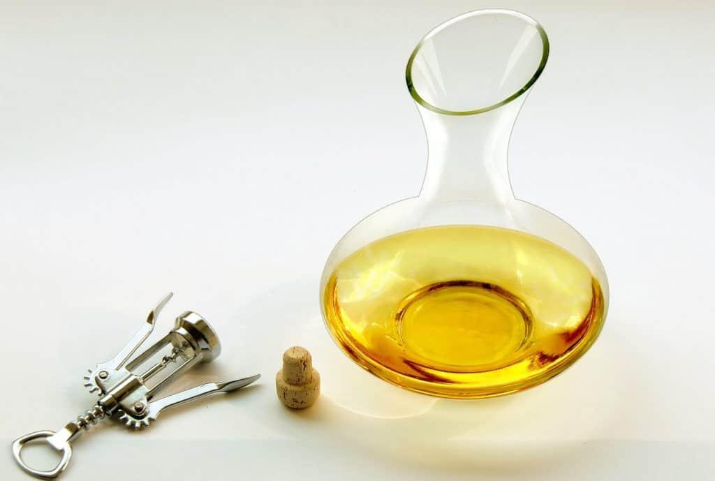 Na foto um decanter com vinho branco e um saca-rolhas e uma rolha ao lado.