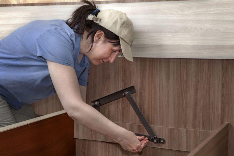 Imagem mostra uma mulher usando uma chave Allen em um móvel.