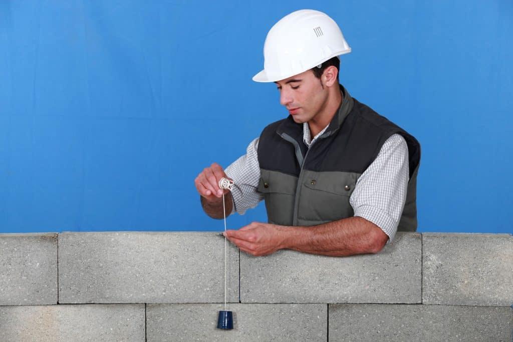 Um pedreiro usando um prumo para medir um pequeno muro de pedras grandes.
