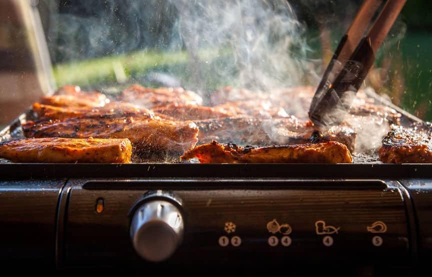 Na foto diversos alimentos sendo preparados em uma churrasqueira.