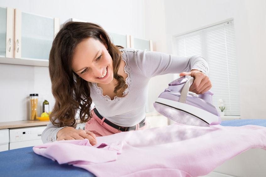 Mãos passando camisa com ferro de passar cor de rosa