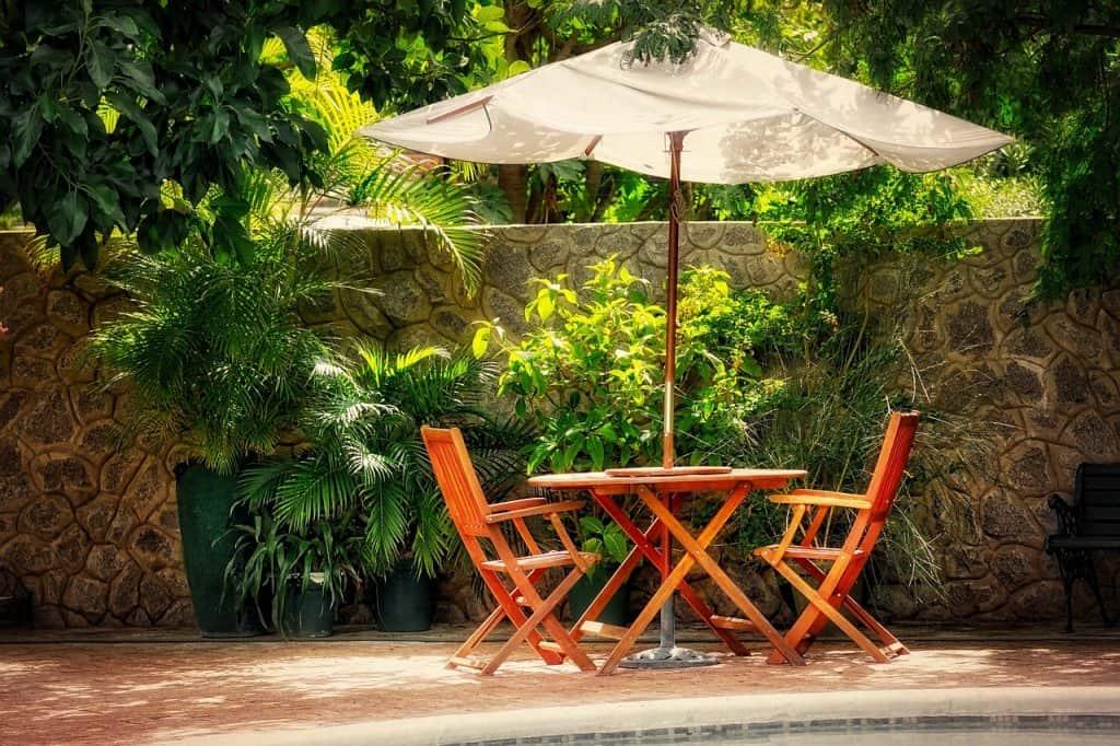 Imagem mostra uma mesa dobrável com duas cadeiras embaixo de um guarda-sol.