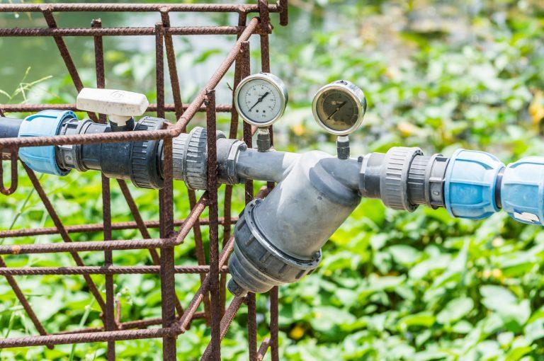Imagem mostra um sistema de irrigação com válvulas e temporizadores.