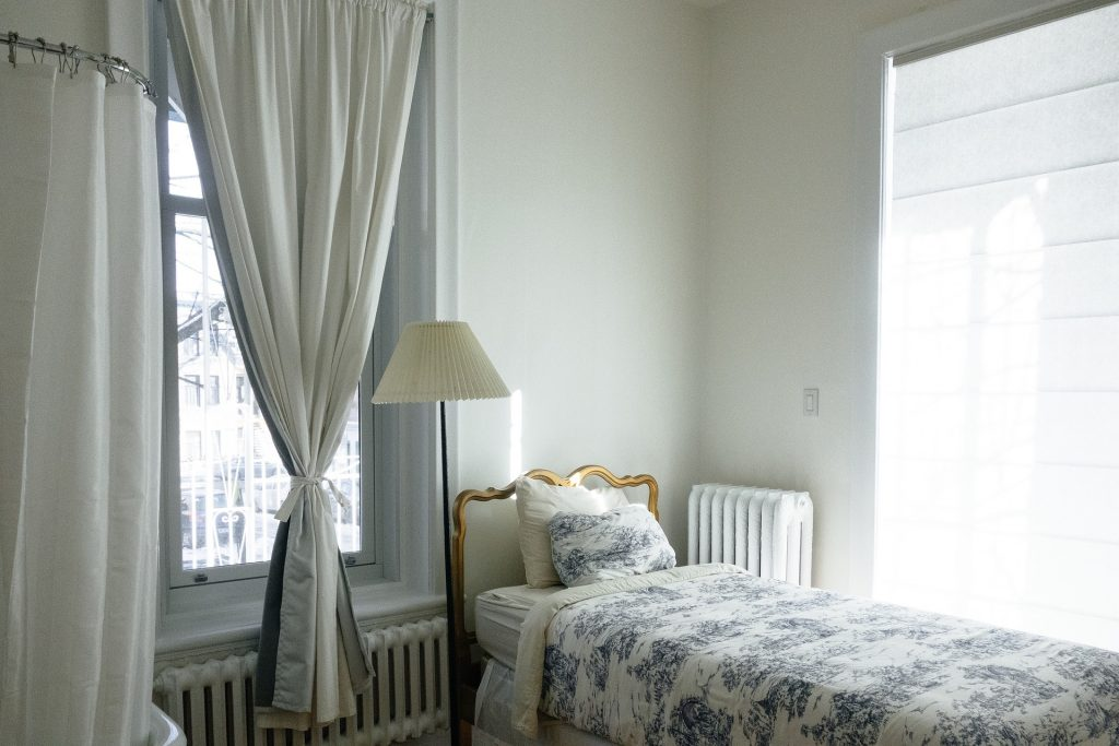 Na foto uma cama com colcha de flores e abajur ao lado em um quarto .