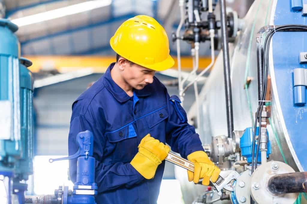 Alt texto: Um operário rosqueando um parafuso de um motor de uma máquina industrial.