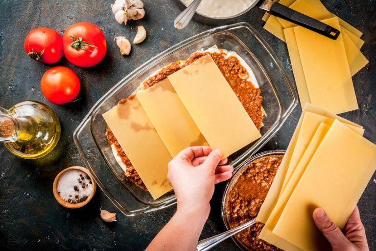 Imagem de mãos preparando uma lasanha em um Marinex.