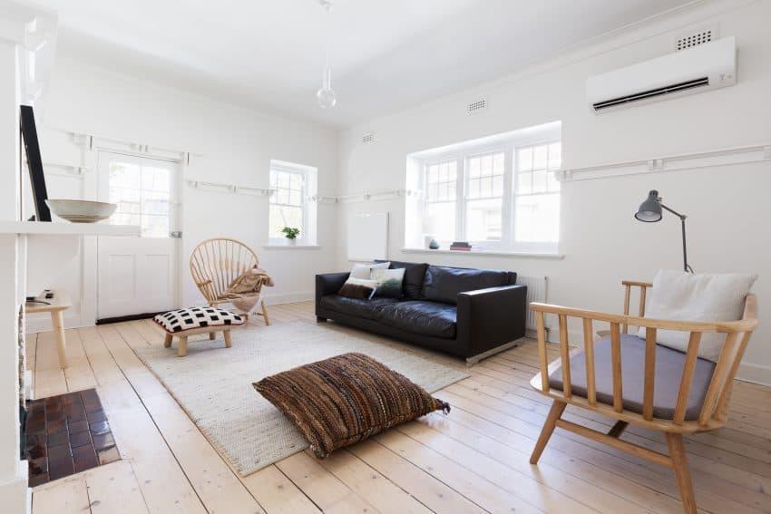 Na foto uma sala de estar com ar condicionado, sofá, poltrona, almofada e tapetes.