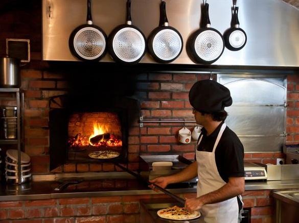 Chef de cozinha colocando pizza para assar em forno a lenha em uma cozinha moderna.