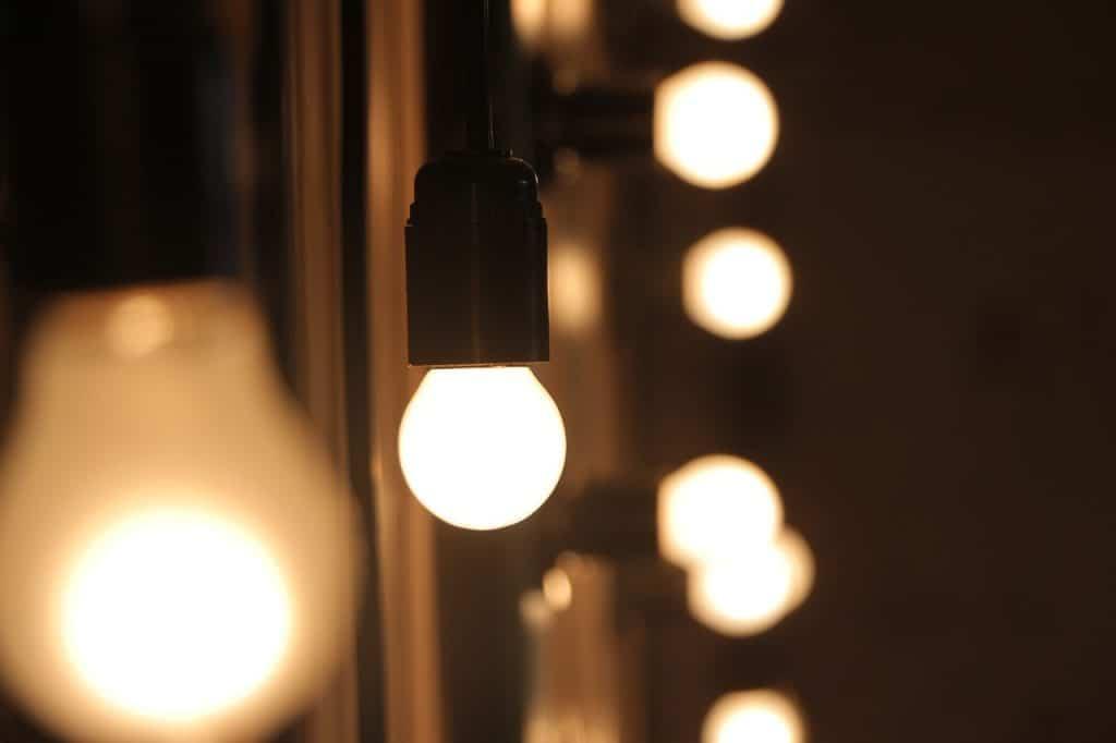 Na foto diversas lâmpadas acessas ligadas em pendentes.